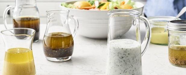 Woman making 7 homemade versatile pantry dressings with a fresh colorful salad on a white marble counter in a beautiful kitchen