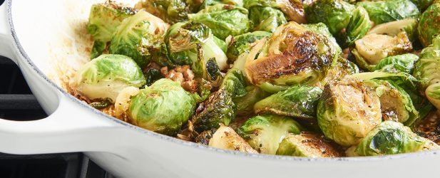 Golden brown candied brussels sprouts in a white skillet on a stovetop