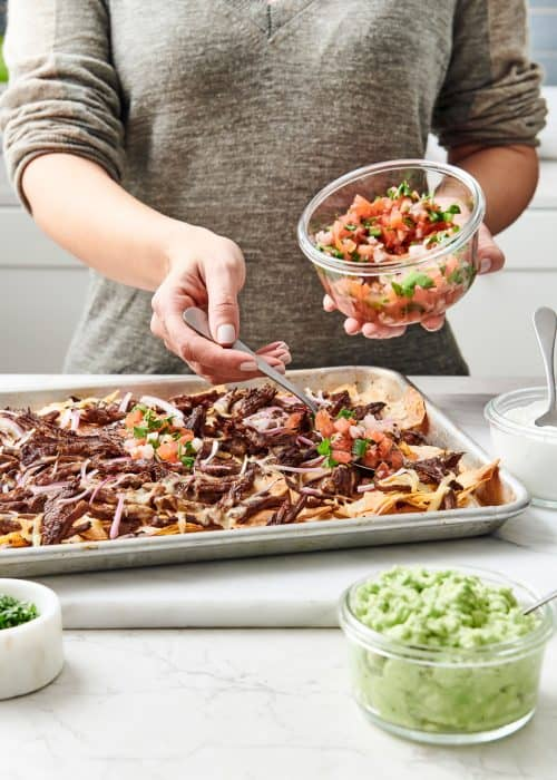 Woman putting pico de gallo on a sheetpan of steak nachos with guacamole on a white marble surface