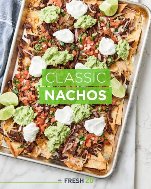 Sheetpan loaded with steak nachos with pico de gallo, sour cream and guacamole on a white marble surface
