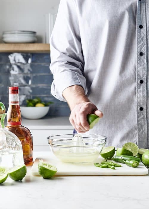 Man juicing lime with jalepeño and liquor in a beautiful kitchen