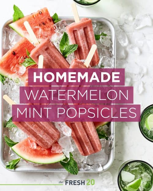 Sheetpan full of fresh watermelon and homemade watermelon mint popsicles with ice on a white marble surface