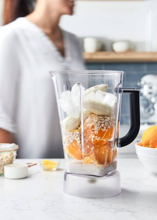Woman making a smoothie with fresh oranges and bananas in a blender in a beautiful white marble kitchen