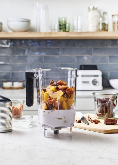 Blender on a white marble surface full of fresh and frozen fruit making tropical peach sorbet in a beautiful kitchen