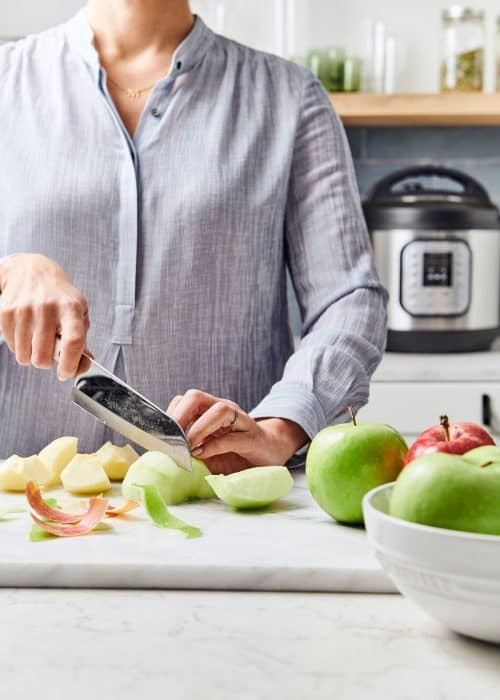 Woman slicing green apples on a white marble surface with an Instant Pot on the back counter in a beautiful modern kitchen