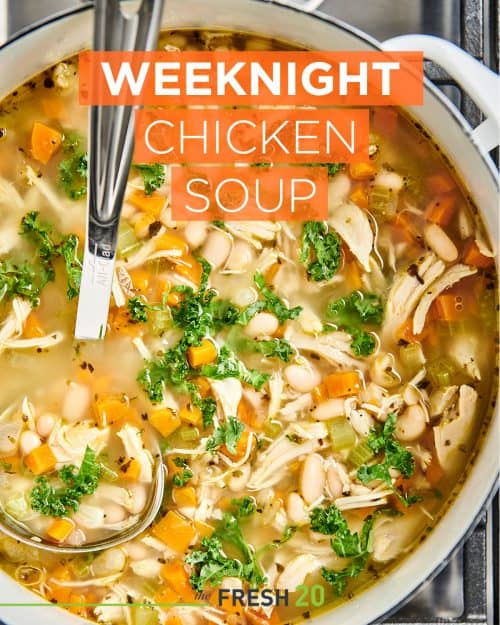 Le Creuset pot of simple hearty weeknight chicken soup with carrots and kale on the stove with a ladle from above