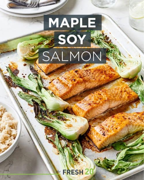 A baking sheet pan loaded with maple soy salmon recipe surrounded with vibrant bok choy and a bowl of rice