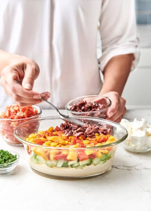 Woman using a spoon to layer olives into a serving bowl to create an easy 7-layer Mediterranean dip for entertaining