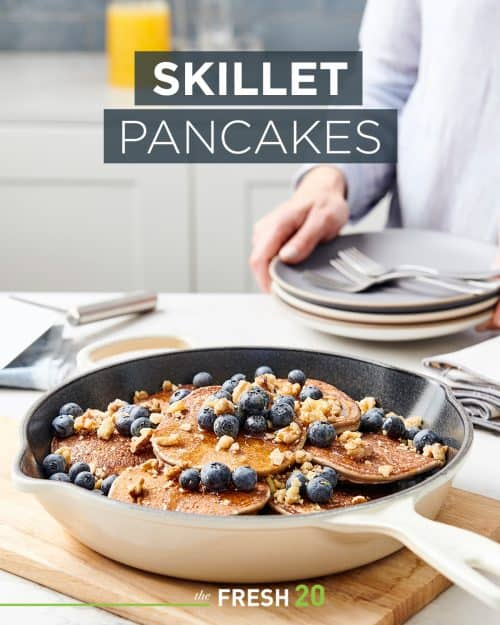 Skillet full of fluffy pancakes with plump blueberries, crushed nuts & syrup in a white marble kitchen
