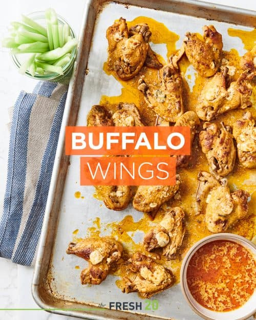 Baking sheet pan full of buffalo wings with a bowl of dipping sauce and celeryon a white marble surface