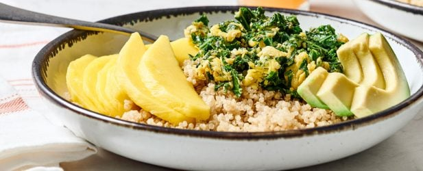 Kale, avocado, quinoa and sliced mango breakfast bowl with a glass of fresh juice on a white marble surface