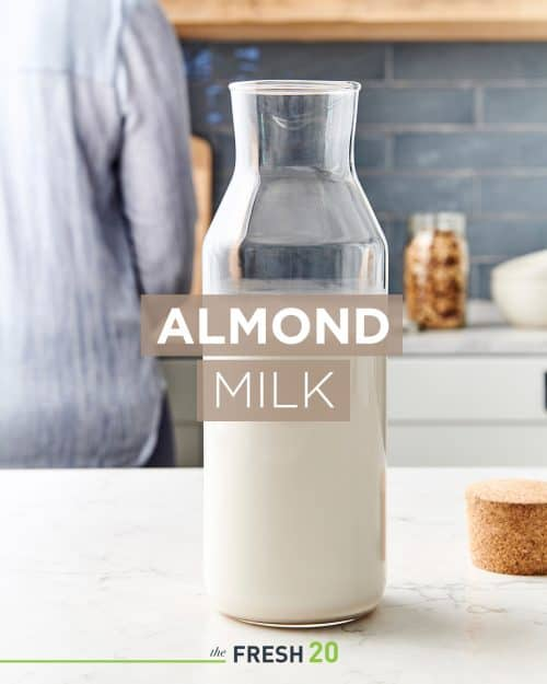 Beautiful tall glass milk jug full of creamy easy homemade almond milk in a white marble kitchen