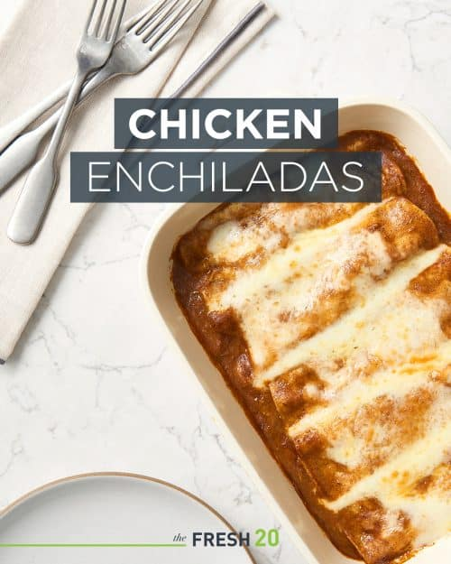 Staub baking dish full of chicken enchiladas & red sauce and melted cheese on a white marble surface with utensils