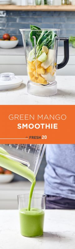 Blender full of tropical fruit & bok choy pouring green smoothie into a clear glass in a white marble kitchen