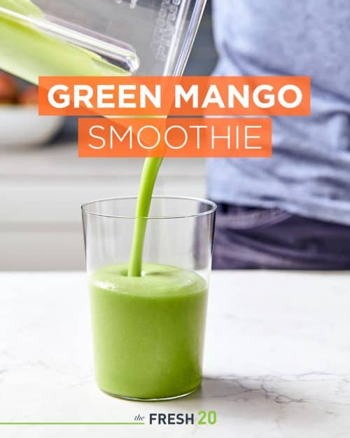 Person pouring tropical green mango smoothie into a clear modern glass in a beautiful white marble kitchen