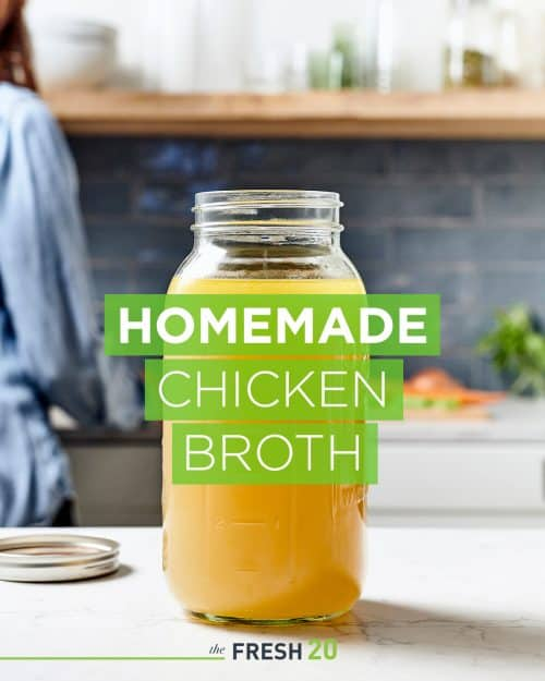Large mason jar filled with fresh homemade chicken broth in a beautiful white marble kitchen