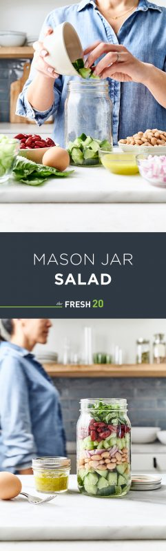 Woman filling & walking by a mason jar full of salad next to a mini jar of dressing & a hard boiled egg in a white marble kitchen