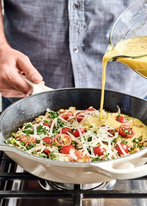 Man pouring egg mixture into a pan full of savory sausage, asparagus, fresh tomatoes, tangy cheese and creamy eggs on a cooktop