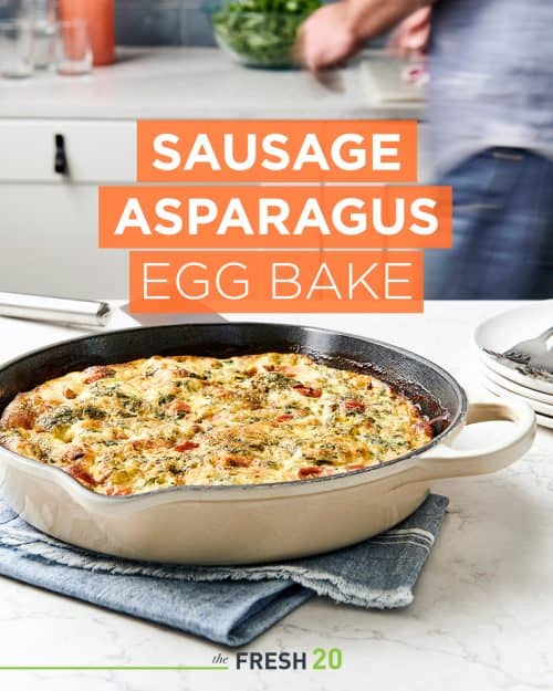 Large metal skillet full of sausage asparagus egg bake on a blue linen napkin in a beautiful marble kitchen