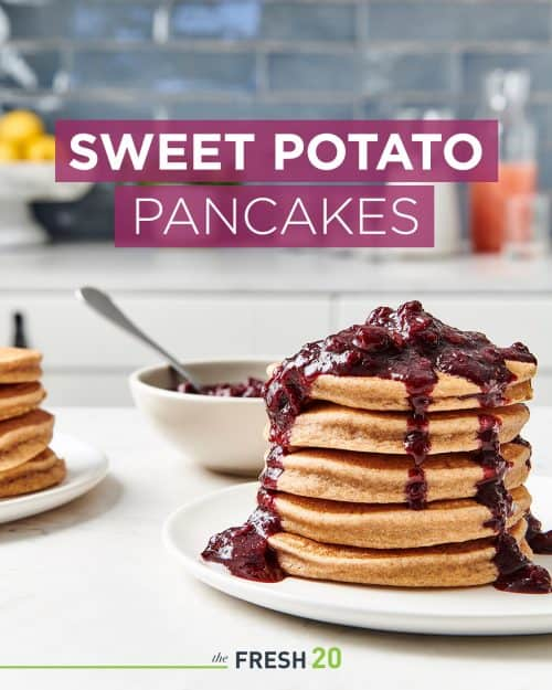 Tall stack of fluffy sweet potato pancakes on a cream plate coated in a thick sweet blueberry compote in a white marble kitchen