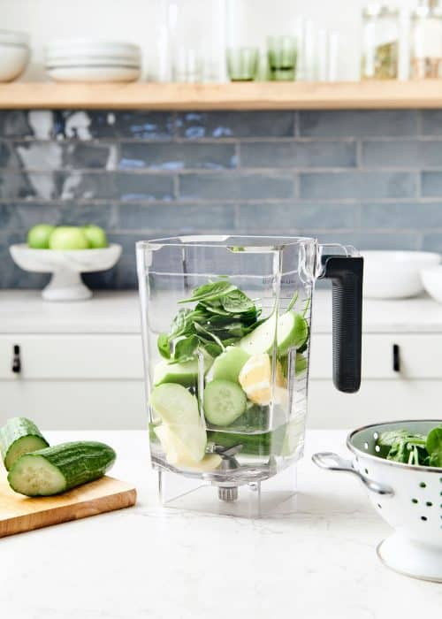 Blender full of fresh cucumber apple ginger green juice fruit & vegetables & a wood cutting board in a beautiful white marble kitchen