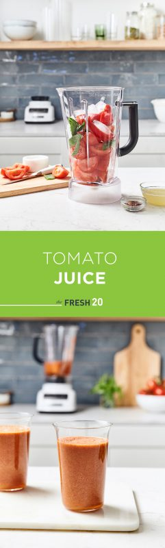 Tall modern glasses full of fresh tomato juice with a blender full of vibrant vegetables in a beautiful white marble kitchen