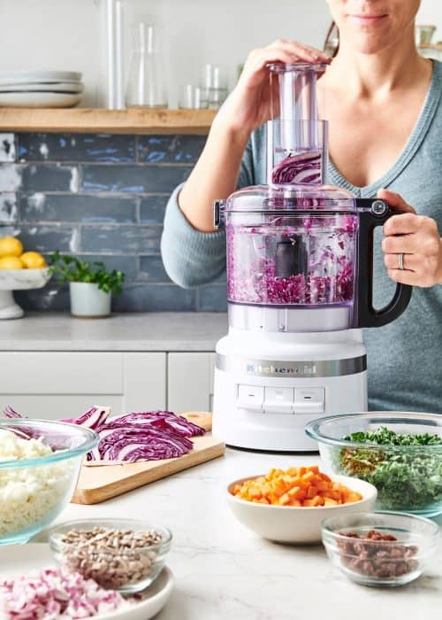 Woman chopping red cabbage in food procesor surrounded with bowls of fresh cut vegetables for a vegan chopped salad in a beautiful white marble kitchen
