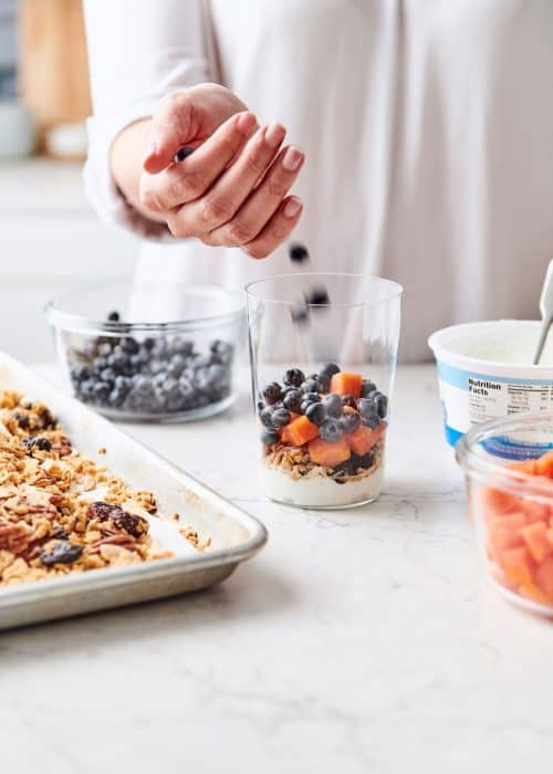 Woman filling a perfect parfait glass with yogurt, blueberries & papaya next to a baking sheet of toasted homemade granola