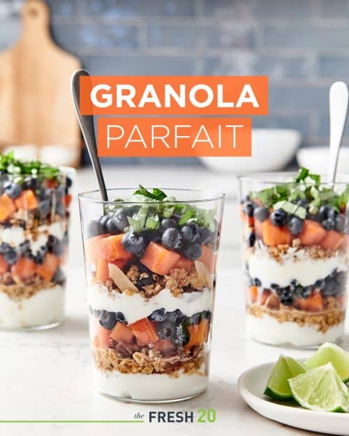 3 parfait glasses filled with layers of homemade granola, fruit & greek yogur in a beautiful white marble kitchen