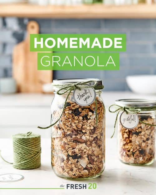 2 mason jars full of decadent homemade DIY granola wrapped with a green twine & a thank you tag on a white marble surface