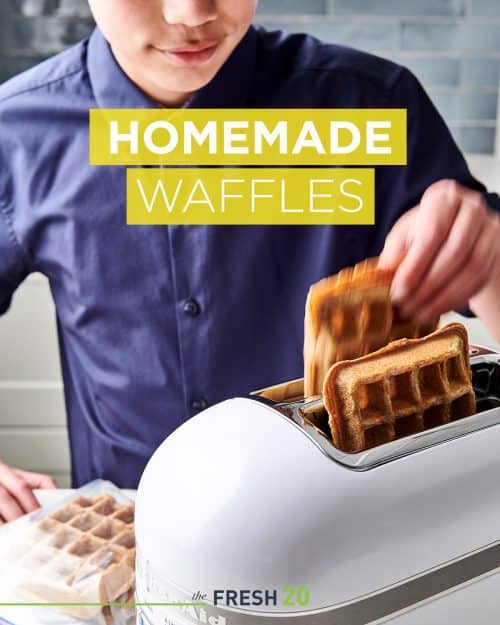Young boy adding DIY homemade waffles into a white KitchenAid toaster in a beautiful kitchen