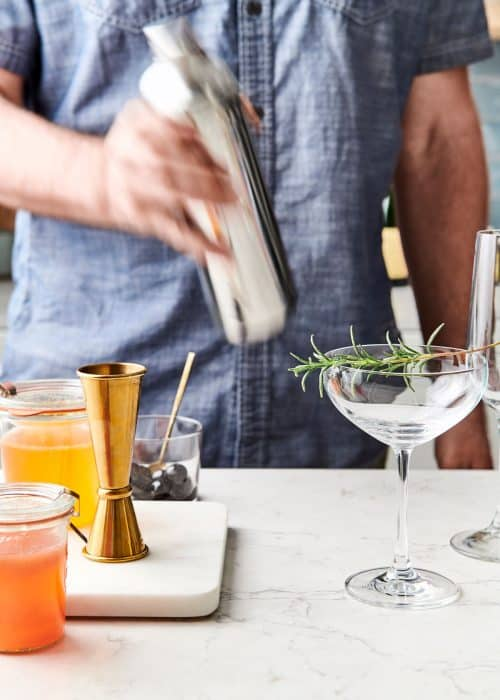 Man making Mother's Day cocktails in a shaker next to a champagne glass garnished with rosemary on a white marble surface