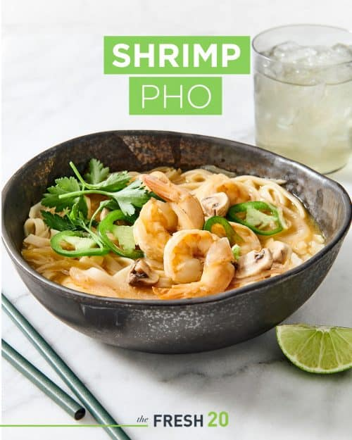 Black ceramic soup bowl filled with suculent shrimp pho with lime wedge, chopsticks & a glass of water on a white marble surface