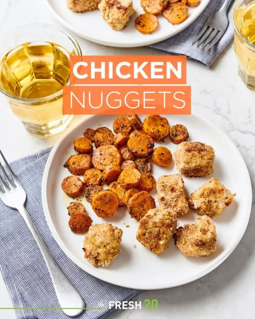 White ceramic plate with crispy baked chicken nuggets & roasted honey carrots with a glass of apple juice and fork on a white marble surface