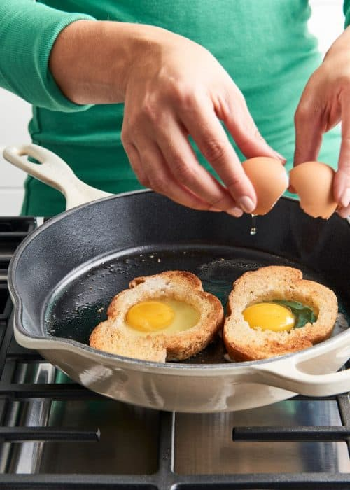 Woman cracking two eggs into two peices of hollowed out toast on a Le Cruset pan on a metal stovetop