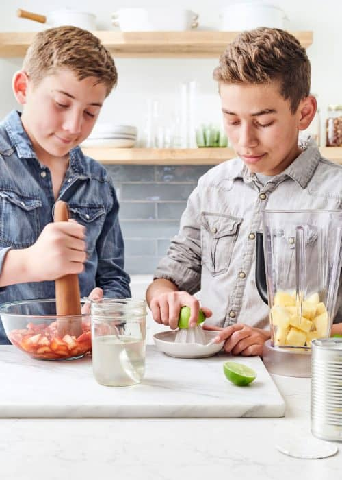 2 young boys muddling strawberries & juicing limes with a pitcher of pineapple in a white marble kitchen
