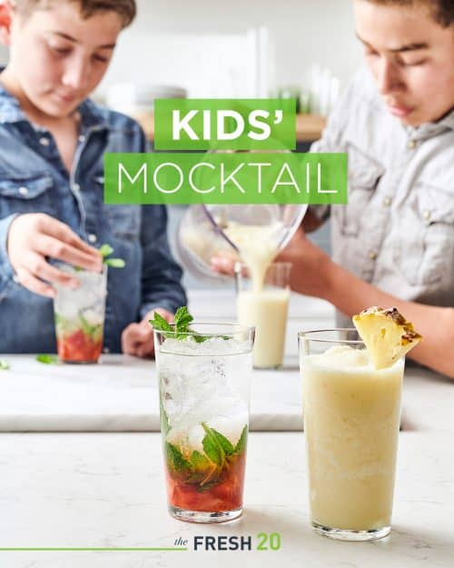 2 boys making 2 fresh fruit summer mocktails with mint leaves & pineapple garnish in a white marble kitchen