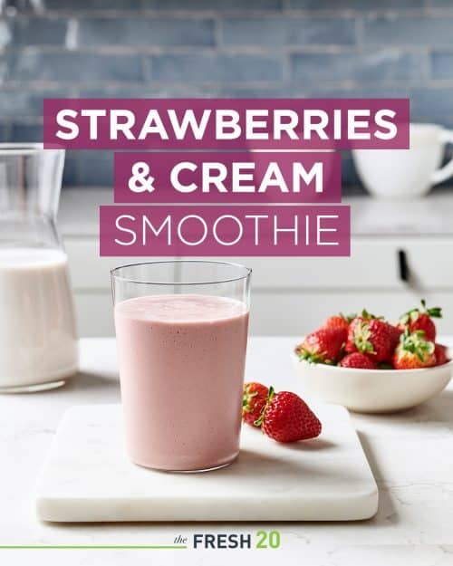 Glass of no sugar added strawberries & cream smoothie with a bowl of strawberries on a white marble surface in a beautiful kitchen