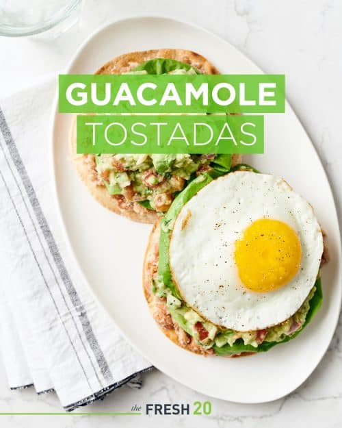Oval plate with 2 summer style guacamole tostadas with lettuce, cheese and sunny side up egg on a white marble surface with a linen napkin