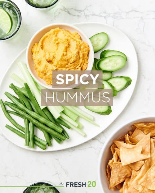 Ceramic plate filled with cucumber slices, green beans & celery with a bowl of spicy hummus & homemade chips on a white marble surface