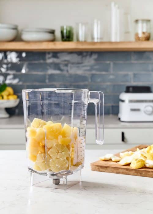 Blender full of yellow lemons & pineapple in a beautiful marble kitchen with a wood cutting board with fruit