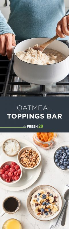 Woman stirring a fresh batch of oatmeal in a white pot with a bowl of oatmeal & a variety of toppings with coffee on a white marble surface