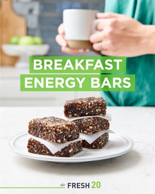No bake breakfast energy bars stacked on a ceramic plate in front of a woman with a cup of tea in a beautiful white marble kitchen