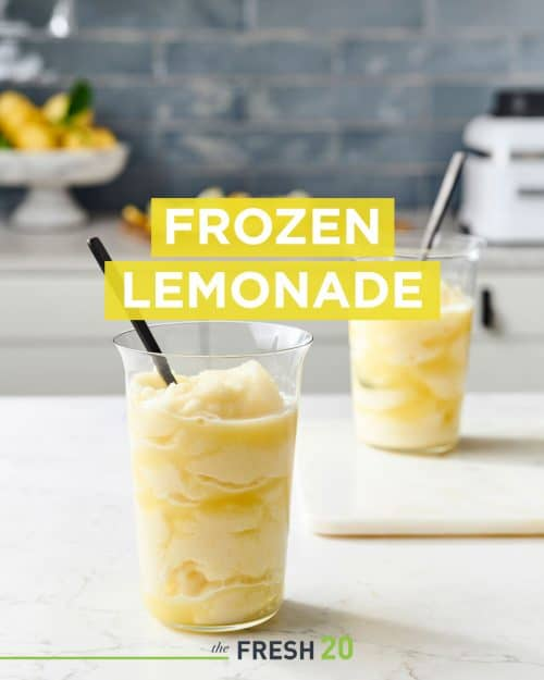 Two modern glasses filled with fresh squeezed frozen lemonade with black spoons in a beautiful white marble kitchen