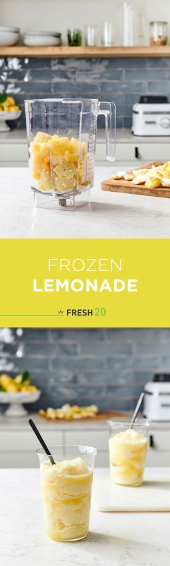 Blender full of fresh lemons & pineapple in a beautiful white marble kitchen with 2 modern glasses of frozen lemonade with lemons on a wood cutting board