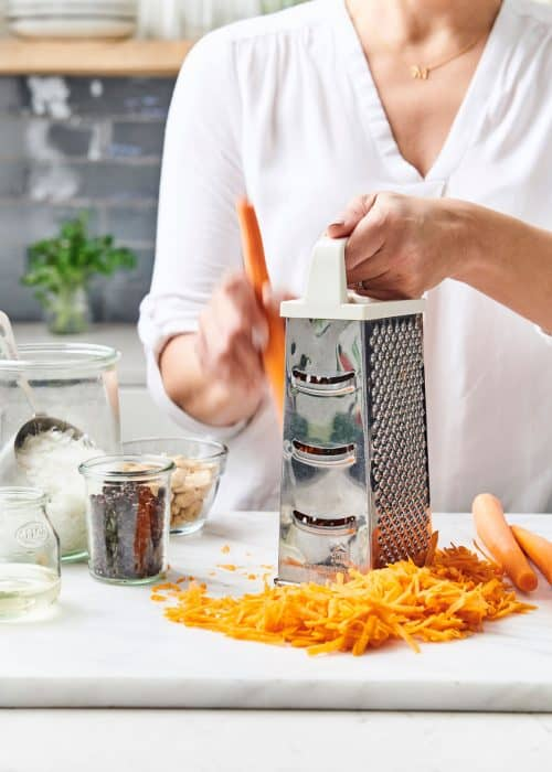 Woman shredding carrots with a metal box grater onto a white marble surface with raisins, coconut & nuts
