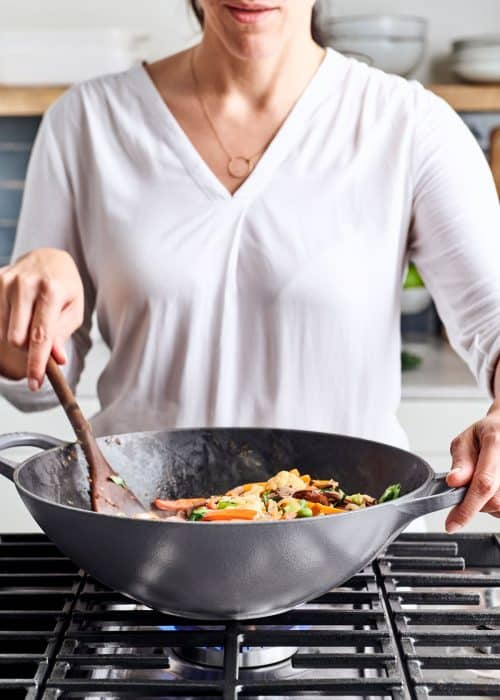 Woman stirring a Le Creuset gray wok filled with 8 vegetable stir-fry on a cooktop in a white marble kitchen