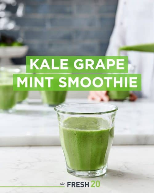Woman making a glass of morning kale grape mint smoothie in a white marble kitchen