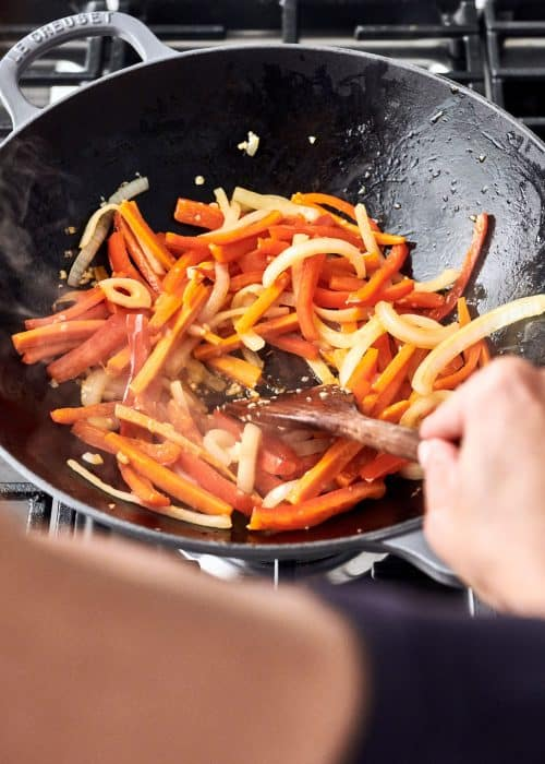 Le Creuset wok filled with carrots, onion and bell peppers being stirred with a wooden spatula on a cooktop