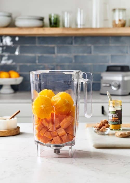 Blender full of oranges & carrots with ginger & turmeric on a white marble counter in a modern kitchen